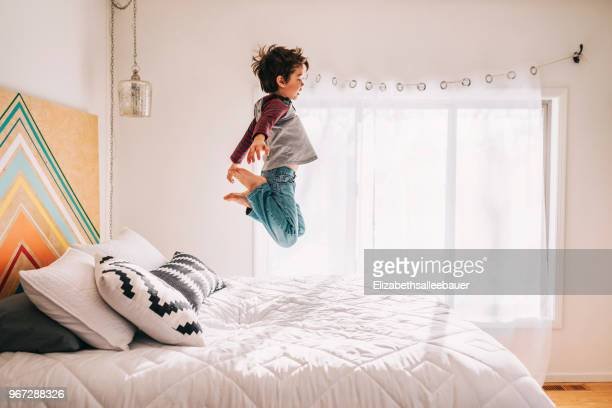 boy jumping on a bed - bed stock pictures, royalty-free photos & images