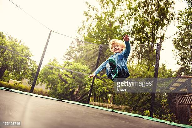 boy jumping on a trampoline - only boys stock pictures, royalty-free photos & images