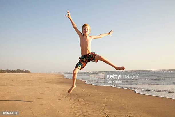 Boy jumping on beach, portrait