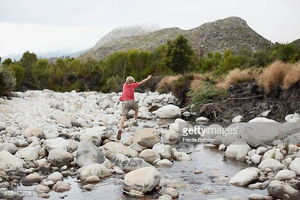 Boy Jumping on Boulders