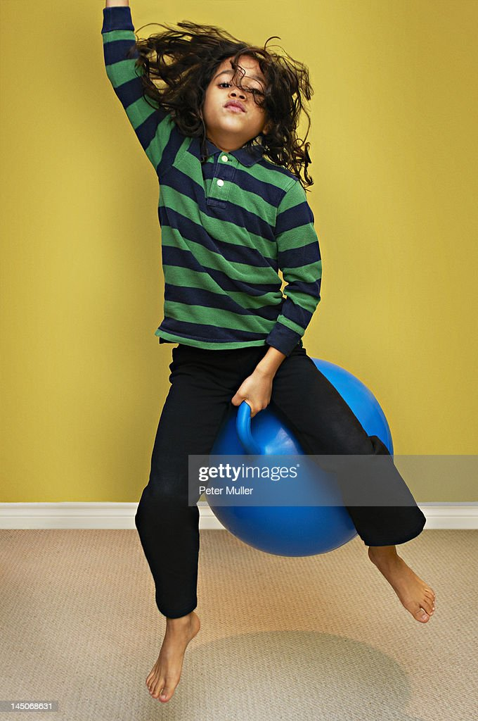 Boy jumping on bouncy ball : Stock Photo