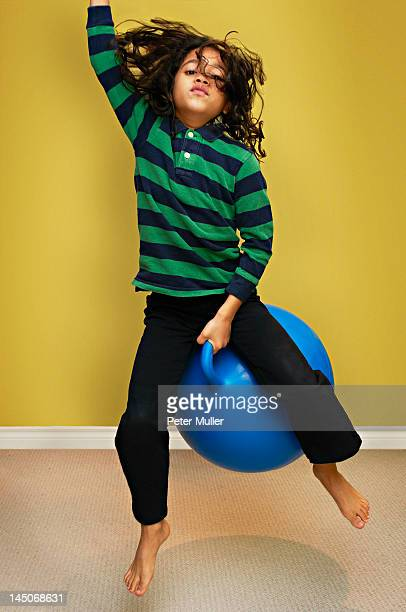 boy jumping on bouncy ball - bouncing ball stock photos and pictures