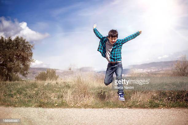Boy jumping on meadow against sunshine
