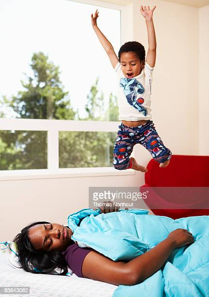 boy jumping on mom in bed