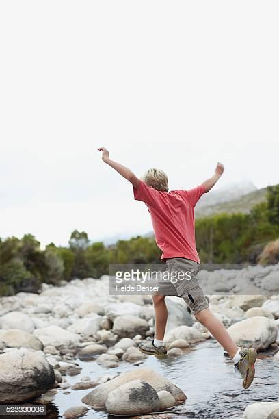 Boy Jumping on Rocks