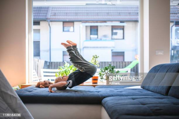 boy jumping on sofa - women's field event stock pictures, royalty-free photos & images