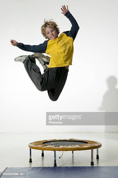 Boy (12-13), jumping on trampoline in studio, portrait