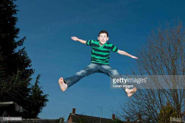boy jumping on trampoline in woking - england - individual event stock pictures, royalty-free photos & images