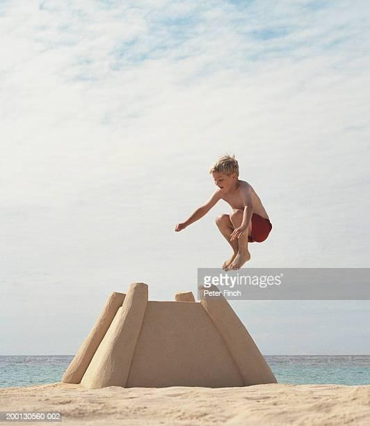 boy (9-11) jumping onto large sandcastle - zerstörung stock-fotos und bilder
