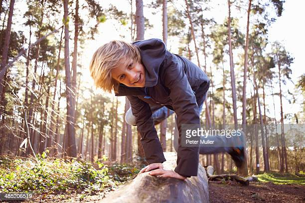 Boy jumping over a tree trunk in forest