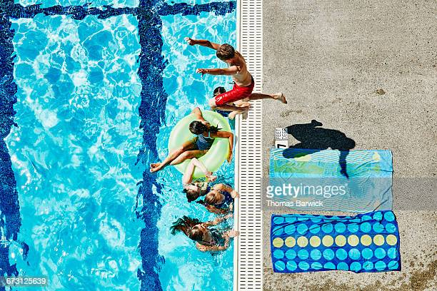 Boy jumping over group of girls into outdoor pool