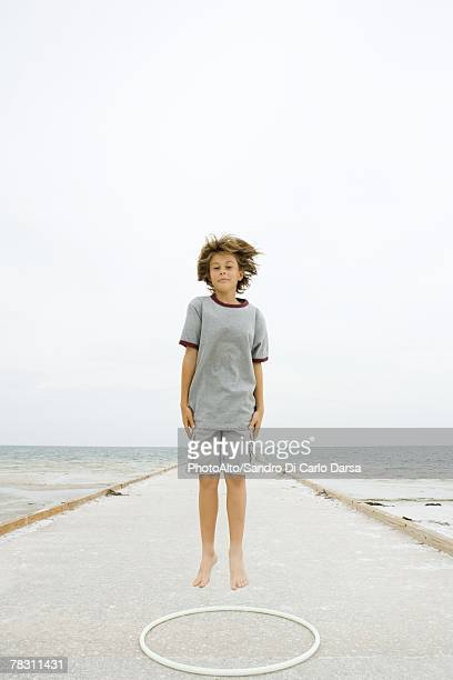 boy jumping over plastic hoop at the beach, smiling at camera - shorts stock pictures, royalty-free photos & images
