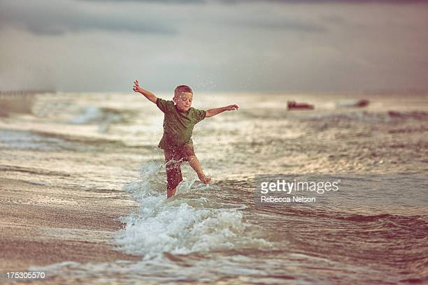 Boy jumping over waves