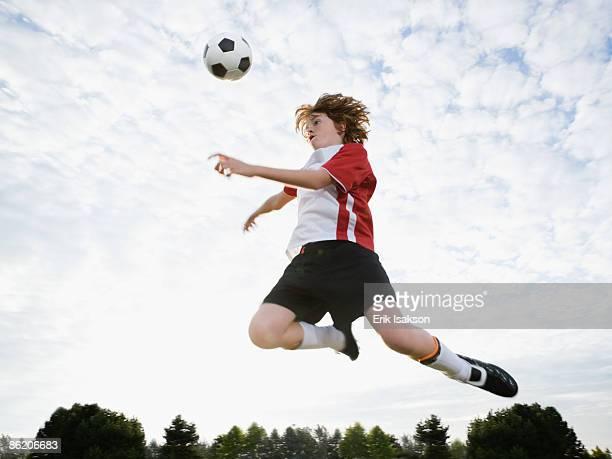 Boy jumping toward soccer ball in mid-air