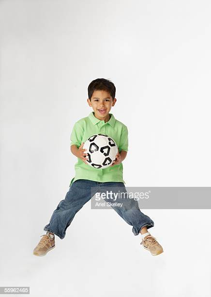 Boy jumping while holding soccer ball