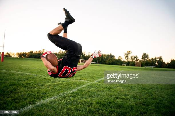 boy jumping with american football on playing field - high school football stock pictures, royalty-free photos & images