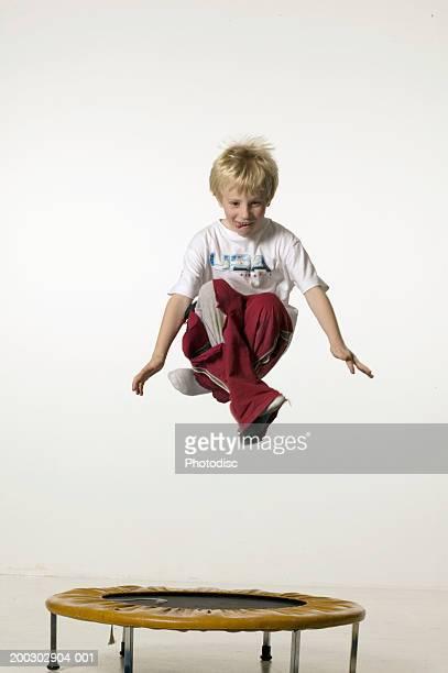 Boy (8-9), jumping with legs crossed on trampoline in studio, portrait