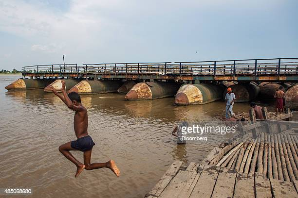 A boy jumps as others bath near a dismantled pontoon bridge on the Ganges river in Raghopur Bihar India on Monday July 27 2015 More than anywhere...