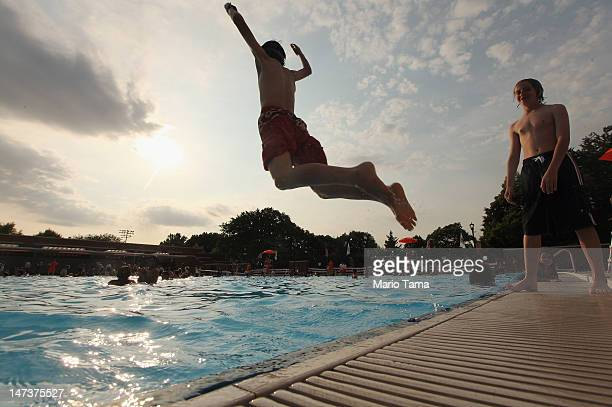 A boy jumps as people bathe on opening day of the newly renovated McCarren Park Pool on June 28 2012 in the Brooklyn borough of New York City The...