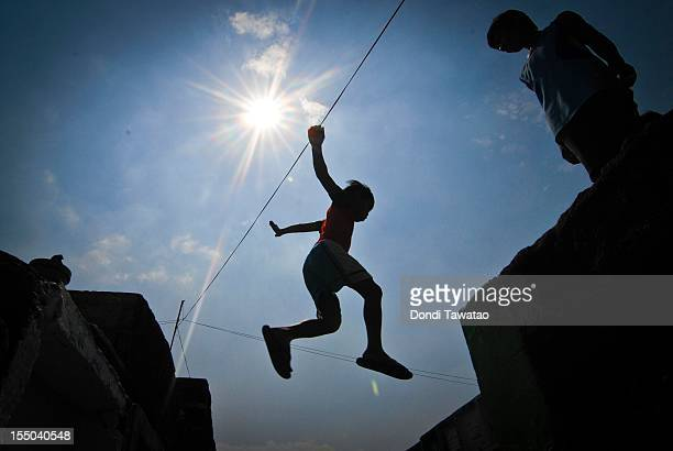A boy jumps between tombstones at the Navotas public cemetery on October 31 2011 in Manila Philippines The 'Day of the Dead 'All Saints' Day' and...