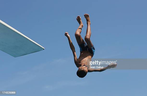 A boy jumps from a diving board at the Freibad Kiebitzberge outdoor public pool on July 27 2013 in Berlin Germany Central Europe is currently...