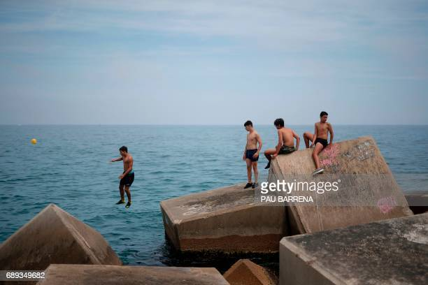 A boy jumps from the breakwater off a beach in Barcelona on May 28 2017 / AFP PHOTO / PAU BARRENA