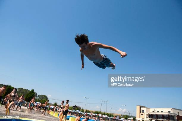 A boy jumps into a pool to cool off in Milosevo on July 11 as temperatures reached 36 degrees Celsius with a new heatwave hitting Kosovo / AFP PHOTO...