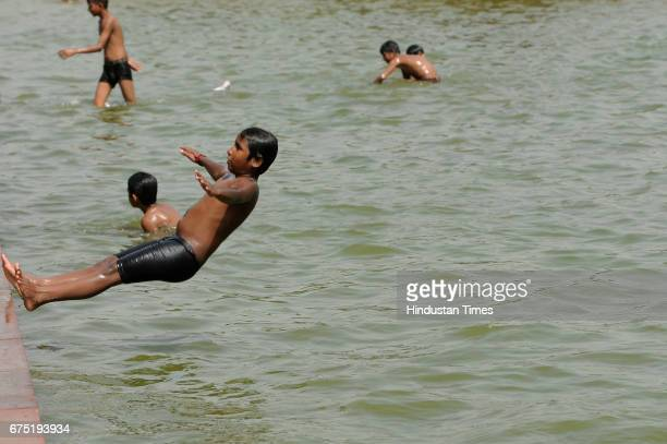 A boy jumps into a water channel on a hot summer day near India Gate on April 30 2017 in New Delhi India