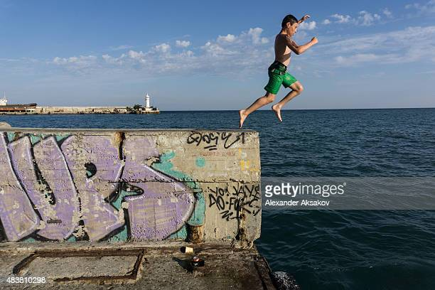 A boy jumps into the Black Sea on August 10 2015 in Yalta Crimea Russian President Vladimir Putin signed a bill in March 2014 to annexe the Crimean...