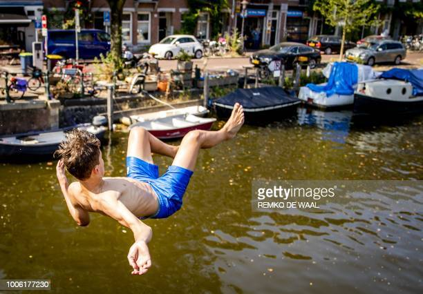 A boy jumps into the Kattensloot canal in Amsterdam on July 27 as a heatwave scorches much of Europe The Dutch meteorological institute on July 26...