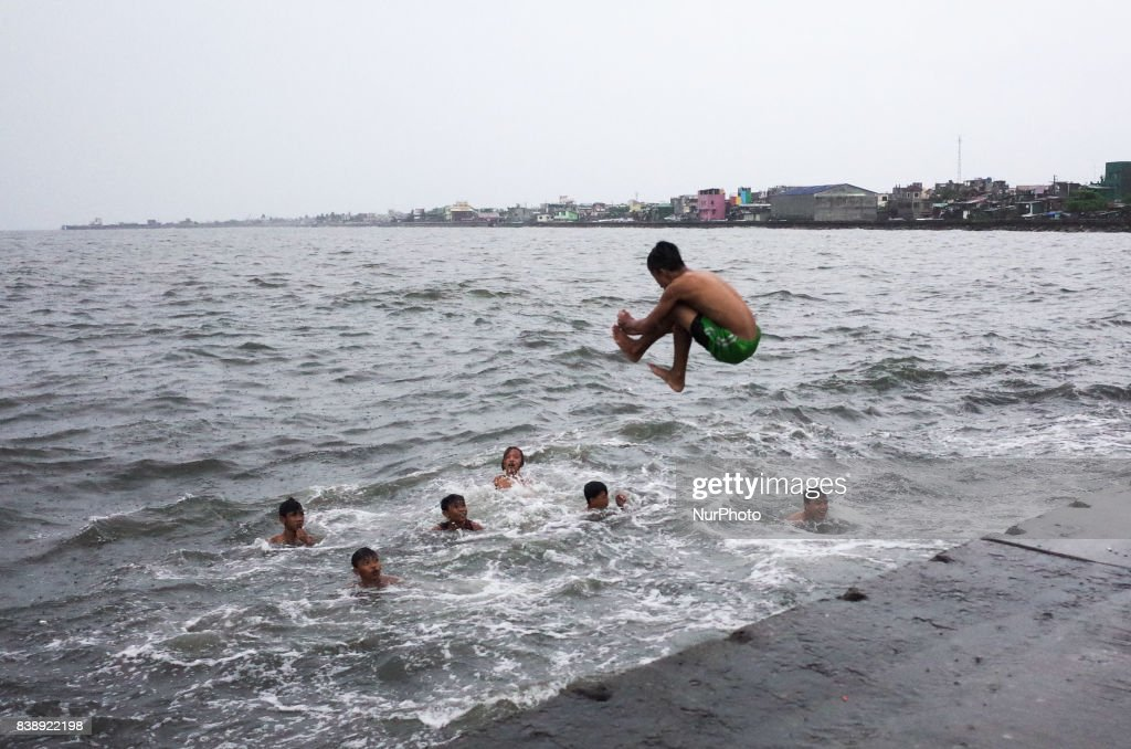 A boy jumps into the Manila Bay as his friends swim among the waves brought by Typhoon Pakhar on Friday, August 25, 2017 in Navotas City, north of Manila, Philippines. Typhoon Pakhar is set to follow the same path as Typhoon Hato, threatening Hong Kong, Taiwan, and northern Philippines with heavy rain and strong winds.