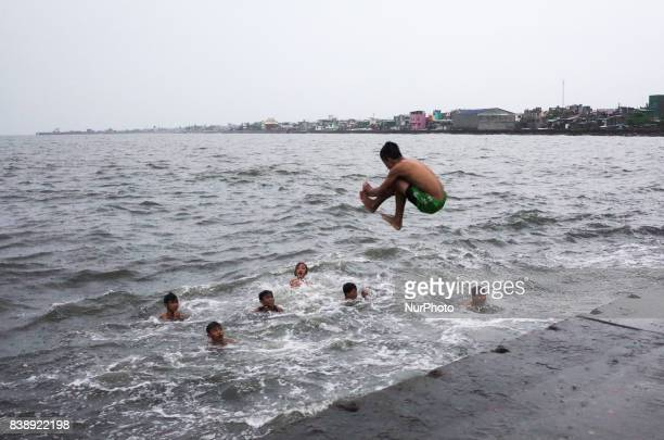 Boy jumps into the Manila Bay as his friends swim among the waves brought by Typhoon Pakhar on Friday, August 25, 2017 in Navotas City, north of...