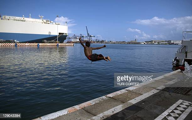 A boy jumps into the water in Veracruz Mexico on October 11 2011 The bodies of four people two men and two women were found in a vacant lot at the...