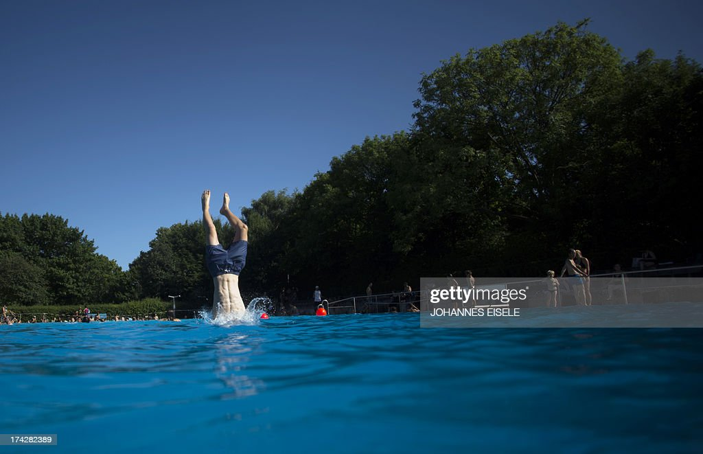 A boy jumps into the water of a public swimming pool on July 23, 2013 in Berlin's Neukoelln district as temperatures in the capital reached 30 degrees Celsius.