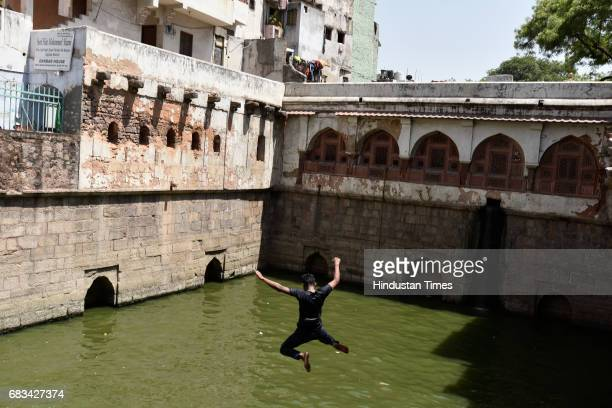 A boy jumps into the water of stepwell at Nizamuddin Dargah on a hot summer day on May 15 2017 in New Delhi India Heat wave conditions prevailed in...
