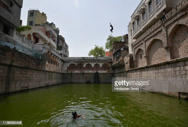 A boy jumps into the waters of a baoli or a stepwell to beat the heat at the Nizamuddin Dargah on April 12 2019 in New Delhi India