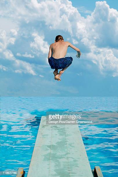 Boy jumps into water