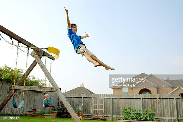 boy jumps off swing in his backyard - courtyard stock pictures, royalty-free photos & images