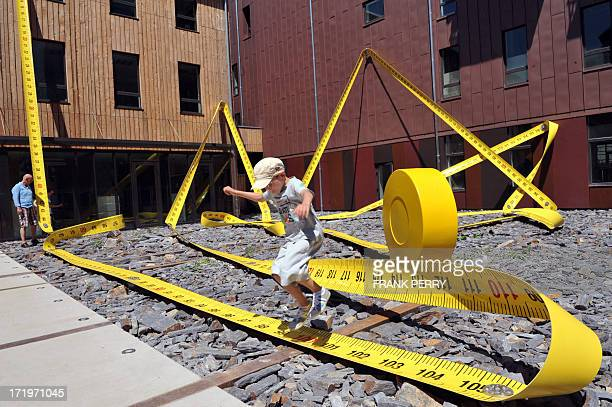 A boy jumps over Lilian Bourgeat's 'Tape Measure' a 136 metre oversized object one of the creations displayed in the centre of Nantes western France...