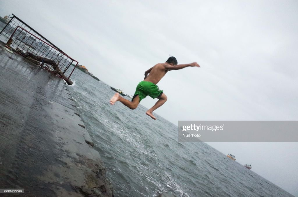 A boy jumps to swim towards the Manila Bay on Friday, August 25, 2017 in Navotas City, north of Manila, Philippines. Typhoon Pakhar is set to follow the same path as Typhoon Hato, threatening Hong Kong, Taiwan, and northern Philippines with heavy rain and strong winds.