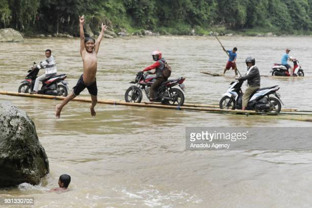 A boy jumps to the river as several people assist motorcyclists to pull up their vehicles onto wooden raft to cross Cisadane River in Rumpin Bogor...