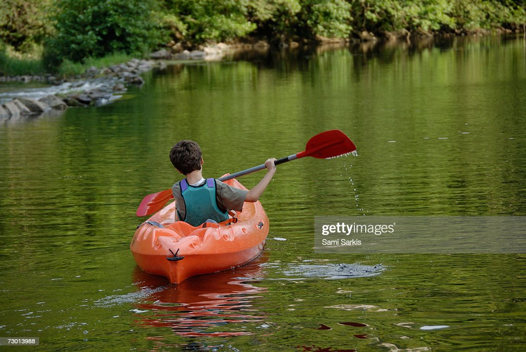 Boy (12-13) kayaking in river, rear view : Stock Photo