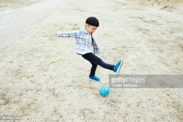 a boy kicking a ball - yusuke nishizawa stock pictures, royalty-free photos & images