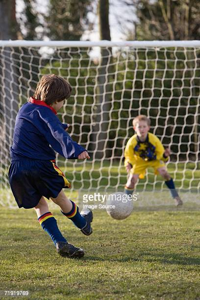 boy kicking a football - kicking stock pictures, royalty-free photos & images