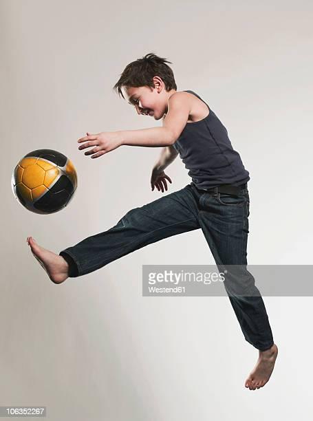 Boy (8-9) kicking ball, smiling