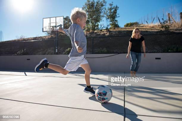 boy kicking ball while playing soccer with mother - mama futbol fotografías e imágenes de stock