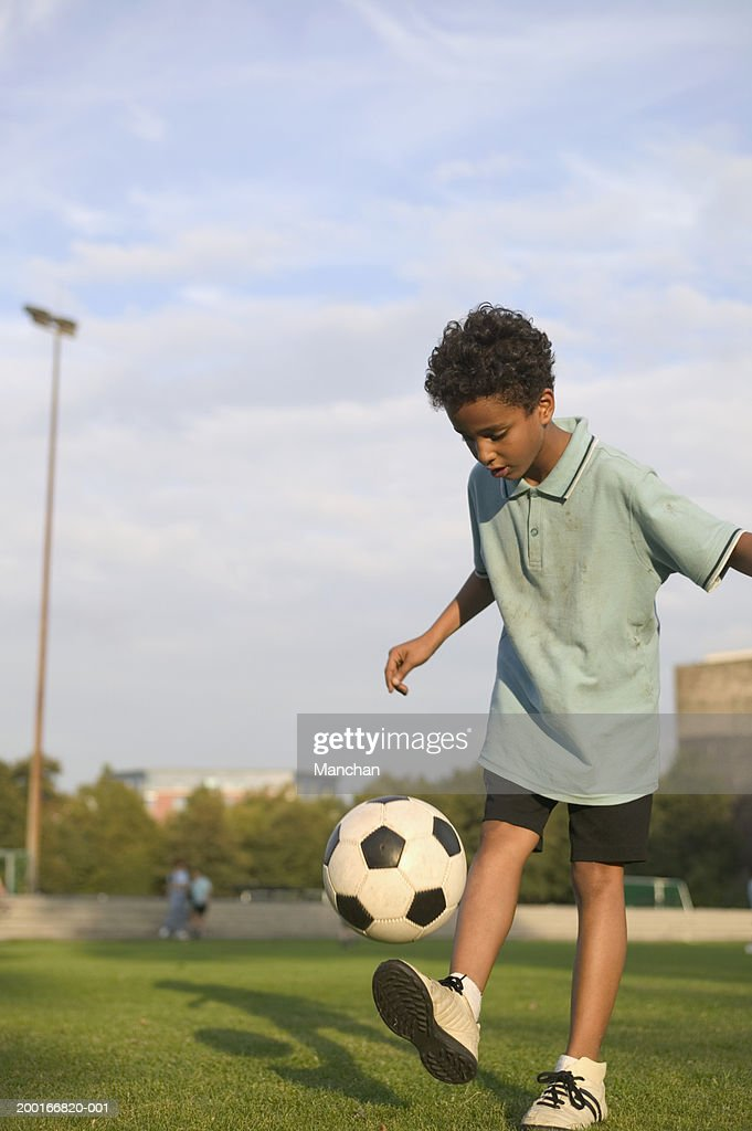 boy kicking football in field stock photo getty images