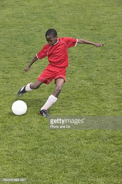 Boy (9-11) kicking football on field