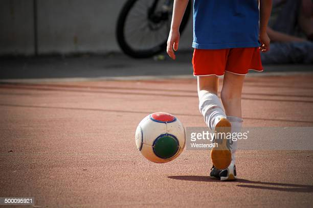 boy kicking football on hard court, partial view - kicking stock pictures, royalty-free photos & images