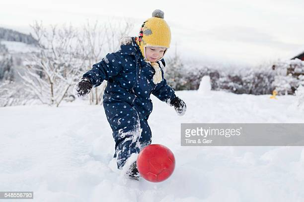 Boy kicking his ball in the snow